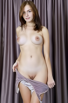 Busty brunette Dakota Pink shows off her beautiful body in a silver leotard that clings to her voluptuous curves